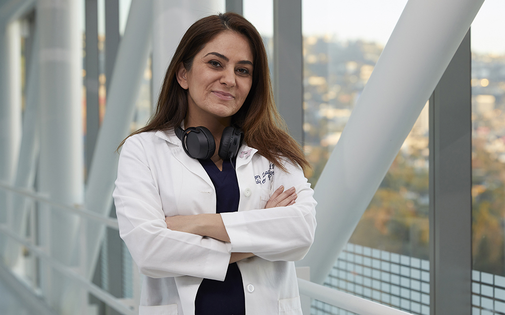 Dr. Karen Zaghiyan, smiling with arms crossed and wearing headphones around her neck.