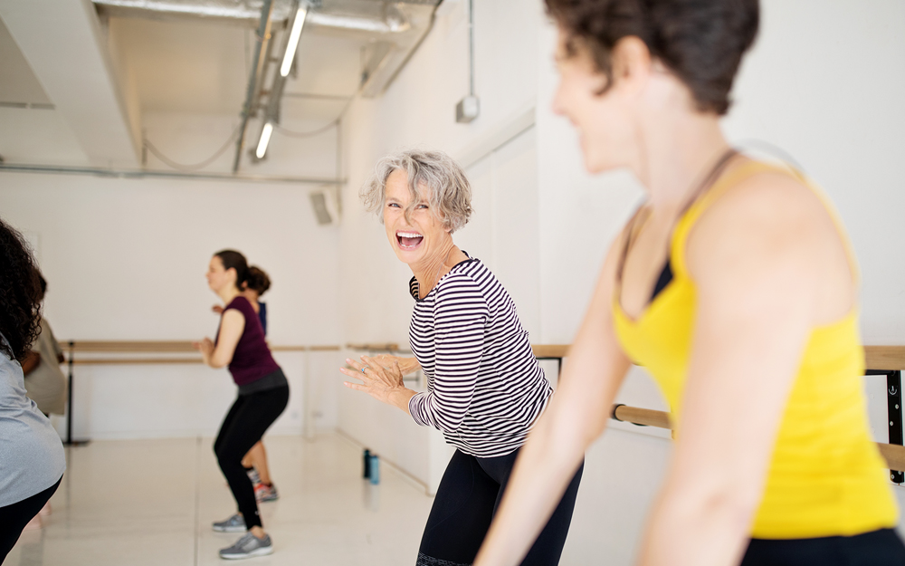 A group of women exercising in a gym in away safe from the effects of high blood pressure.