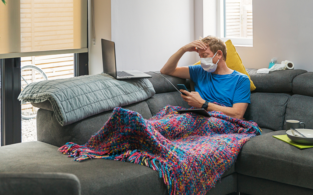 A man sick at home sitting on the couch wondering if he has COVID-19, the flu or a cold.