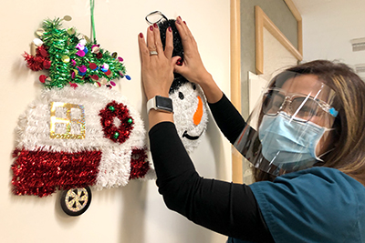 A nurse hanging up a snowman decoration on a wall next to several other decorations