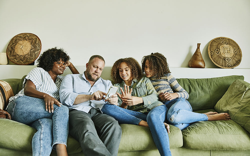 Family sitting on couch in living room looking at smart phone
