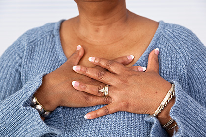 Woman with hands over chest